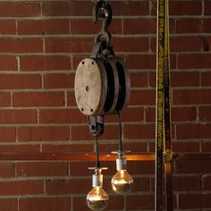 "Reclaimed, repurposed industrial vintage wooden block & tackle pulley pendant lends dramatic lighting to daring decors. Each piece is one of a kind. Sizes will vary. Some with hook and some with loops. 100 watts. UL approved. Welded hook.(27""Hx8""W)"