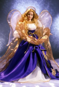 Holiday Angel Barbie® Doll | Barbie Collector :: Barbie® looks lovely in a flowing ensemble, shimmering with golden highlights. Her angelic gown is made of an ivory shirred bodice accented with puffed sleeves, and a royal blue, full skirt, which opens in front to reveal a sheer white underskirt. The lovely gown is embellished with golden braid trim. A golden stole swirls all around her glittering ivory wings and golden halo. Release Date: 10/1/2000