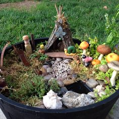 Our Fairy Garden! Has a bark house with a bell, a mushroom forest, a birdbath made from a drawer pull, sculptural metal yard art (from soldering scraps), a rock pond, a playground with a slide, and a corked bottle of gold glitter fairy dust!