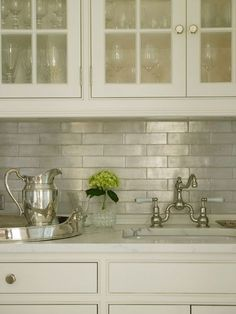 kitchen backsplash Glass-front upper cabinets and ivory lower cabinets paired with white marble countertops and iridescent tile backsplash laid out in brick pattern framing sink with vintage style bridge faucet. Kitchen Redo, New Kitchen, Kitchen Remodel, Kitchen Design, Kitchen White, Narrow Kitchen, Kitchen Stove, Kitchen Pantry, Vintage Kitchen