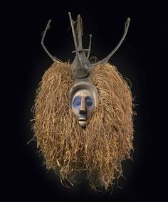 Africa | A hand mask, wood, textile, bast fibres, coloured white, blue, red and black. This imaginative type of mask appears at initiations among the Yaka in south-western Congo. These masks have flat backs and are held by a handle with one hand in front of the mask dancer's face. This piece exhibits the characteristic upturned nose of all sculptures and carvings of the Yaka – the typical 'Yaka-nose'.