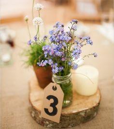 un centrotavola ecologico: legno, un boccaccio come vaso, una candela..