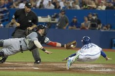Toronto Blue Jays' Josh Donaldson, right, slides into home to score past Cleveland Indians catcher Yan Gomes after a sacrifice fly from Blue Jays' Troy Tulowitzki during second inning AL baseball action in Toronto on Wednesday September 2 , 2015. THE CANADIAN PRESS/Chris Young