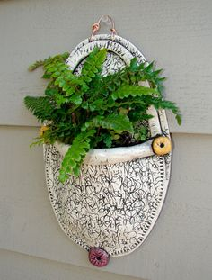 This Textural Pottery Wall Vase holds a small plant and will add an element of eclectic interest to your patio, deck, porch, etc. Made from lowfire