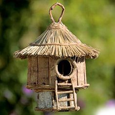 charming birdhouse made of sustainable wood and vine with a grass roof and sweet steps to the front door.