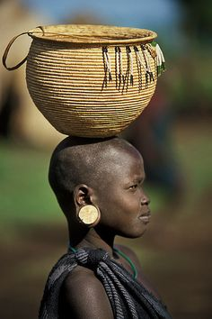 Africa | A young Mursi Girl with a beautiful basket on her head.  Lower Omo valley  Ethiopia
