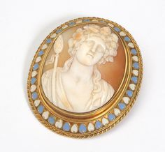 14K gold frame brooch with enamel accent centering a shell carving of Greek god Baccus , est:$200/400