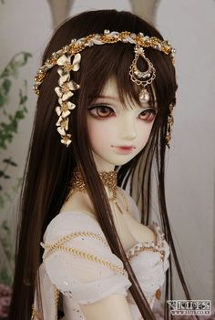 Ball jointed doll with golden fantasy styled head piece and clothing.