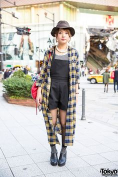 This is Satomi, a friendly beauty salon staffer who we met on the street in Harajuku. Satomi's look includes a Sly romper over a striped t-shirt from the same brand, with a long checkered resale coat on top. Her red backpack is from Moussy. She is also wearing a hat, earrings, a pearl necklace, minimalist rings and bracelet, and heeled ankle boots. She told us her accessories are resales. (Tokyo Fashion, 2014)