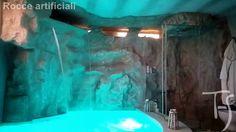 Rocce artificiali con cascata su piscina interna.