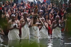 A Nepalese Hindu priest, center, carries the idol of a deity as devotees get ready to take a holy dip at the Salinadi River on the first day of Madhav Narayan festival, in Sankhu, northeast of Katmandu, Nepal. (AP)