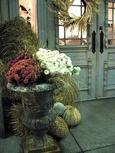 Urn full of potted mums and spent grass from the summer flowers. Excellent continued use of spent foliage!