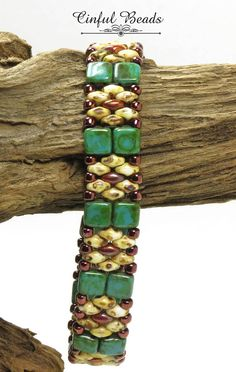 An adorable hand beaded bracelet utilizing white picasso and copper SuperDuos, turquoise picasso Czechmate Tiles, and dark bronze Toho seed beads. The tiles are woven side by side and alternate with a SuperDuo floral design to make a very stylish bracelet. The clasp is a
