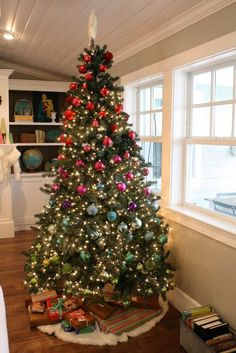 christmas house tour at the pleated poppy - ornaments in color gradation down the tree - metal basket for books