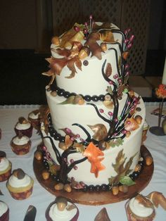 Drum Fall Wedding - This was a topsy turvy fall wedding cake done in buttercream with fall leaves and acorns made from fondant and caramels.  Even though the vine/branch looks very dark, it was just the chocolate fondant with a bit of aztec gold highlights. The leaves were also brushed with a few different colors of luster dusts.  160 cupcakes adorned with the same fondant accents went with this one!  A variety of cake flavors were used, banana, pumpkin spice, red velvet and carrot.