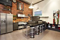 kitchen idea- love the brick wall with stainless fixtures