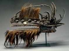"Mali; Bamana peoples (Koulikoro region) Warakun or Kòmòkun (Kòmò Association Helmet Crest Mask) Wood; animal fur; porcupine quills; duiker, oribi, and roan antelope horns; feathers; mirror; sacrificial patina 44.4 x 76.2 x 35.4 cm (17 1/2 x 30 x 10"") New Orleans Museum of Art: Gift of Kent and Charles Davis,"