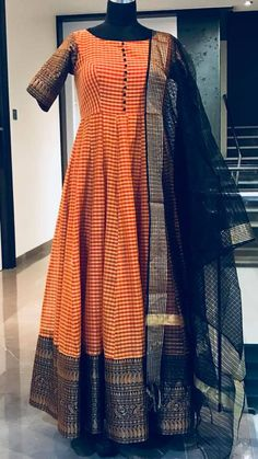 Beautiful ornage and cream color combination checked floor length ananrkali dress with black net dupatta. Ananrkali dress with big pattu boarder and sleeves. To order whatsapp Indian Gowns Dresses, Indian Fashion Dresses, Indian Designer Outfits, Designer Dresses, Designer Wear, Long Dress Design, Stylish Dress Designs, Anarkali Dress, Lehenga
