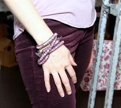 Pink bracelet with burgundy cords.