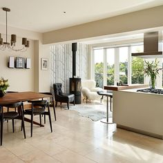 Open-plan kitchen with woodland feature wallpaper, neutral flooring, neutral island unit, wood worktop and wood table