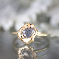 Lovely gray-purple teardrop shape sapphire embedded in a recycled 14k solid yellow gold nugget. I hand-formed the nugget into an organically shape - size 9