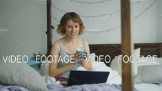 Attractive young woman having online video chat with friends using laptop camera while sitting on bed at home. Student #laptop