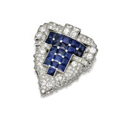 SAPPHIRE AND DIAMOND CLIP, CIRCA 1930 The shield-shaped clip decorated centrally with a panel of French calibré-cut sapphires, bordered by 125 old European-cut and single-cut diamonds weighing approximately 7.00 carats, mounted in platinum.