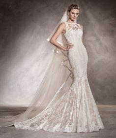Aura— свадебное платье силуэта «русалка», с круглым вырезом под горло, выполненное из тюля и украшенное драгоценными камнями.