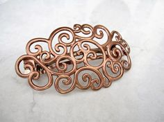 Simply pretty hair clip in rose gold with swirly design. This clip is not recommended for thin hair.  This barrette is 3 1/4 inches long and 1 3/4 inches wide.