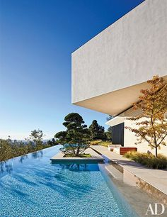 A sparkling infinity pool borders the home's main level; the outdoor furniture is by James Perse.