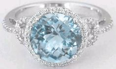 Featuring a lovely 8mm round aquamarine and laden with micropave set diamonds, this beautiful ring is both decidedly feminine and right on trend as well. The aquamarine has a perfect light sky blue color, not too light and washed out and not too dark so that it looks like a blue topaz. This is the perfect color for aquamarine. (MyJewelrySource item GR-1113)