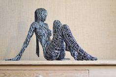 Scultura in filo di ferro: donna che guarda l'orizzonte