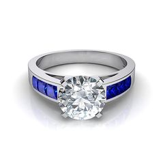 Blue Sapphire and Diamond Engagement Ring. Channel-set, princess cut blue sapphires on a cathedral styled ring enhances any center diamond of your choice. Holiday Sale: $1,480 (40% Off). https://www.nataliediamonds.com/product/blue-sapphire-diamond-engagement-ring/ #NatalieDiamonds #engagementring #bluesapphire