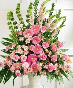 Beautifully arranged, this urn is brimming with all pink flowers - roses, Gerbera daisies, carnations, snapdragons and alstroemeria - accented with Bells of Ireland and assorted greens. A splendid tribute. Casket Flowers, Altar Flowers, Church Flowers, Funeral Flowers, Tropical Flower Arrangements, Church Flower Arrangements, Funeral Arrangements, Types Of Purple Flowers, Pink Flowers