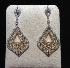 Going out? You'll need these pretty 14k white gold open pear-shape drop earrings with yellow gold twist details and 1.30 cts of diamonds! Only at Becker's!