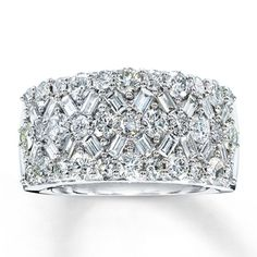 Three rows of brilliant round-cut diamonds are interspersed with diagonal rows of baguette diamonds in this stunning diamond anniversary ring for her. This fine jewelry ring is set in classic 14K white gold and is a generous 10mm in width. The total diamond weight is 2 1/6 carats.