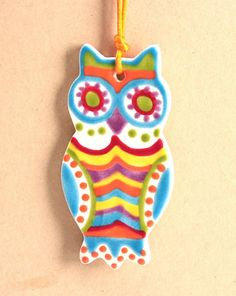 We roll out a clay slab, cut with an owl cookie cutter, drill hole, dry, clean, fire, then paint with glazes, fire, and finish with a colorful cord for hanging.