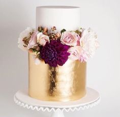 Gold and White two tier cake with gorgeous warm blooms @cake_ink