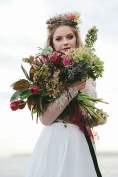Boho beach bride wedding day style with crimson bouquet and flower crown | Little Black Bow Photography | See more: http://theweddingplaybook.com/coastal-bohemian-wedding-inspiration/