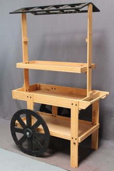 This wood display cart is 42 x 26 x 68 (L x W x D). The stand is made of solid pine with an oak finish and has plenty of storage room to showcase merchandise. This wood market cart has lips on the she Woodworking Projects Diy, Wood Projects, Bar Sala, Food Cart Design, Wood Cart, Kayak Storage Rack, Craft Booth Displays, Store Displays, Sweet Carts