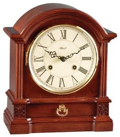 "Hermle Hollins Barrister style mantel clock by Hermle in an elegant cherry finish. Fluted molding, starburst carvings and brass handled drawer. Ivory colored dial with black Roman numerals. Mechanical brass 8-day key wound 1/2 hour strike movement with two bells.  Measures: H 10"" x W 8-3/8"" x D 4-1/2""   Three year manufacturer's warranty   Free shipping within the contiguous United States"
