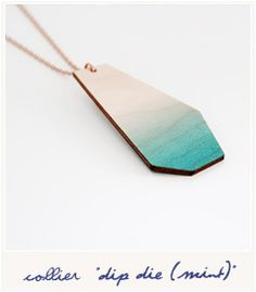 Un pendentif géométrique et néon imaginé par Snug. Fabriqué en bois de bouleau, il a une texture vraiment originale qui se marie parfaitement avec un dégradé de couleur pour lui donner un style totalement unique. Il est tenu par une chaîne dorée à mailles fines.