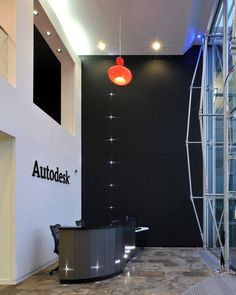 This office reception area at Autodesk has an impressive double height ceiling which is accentuated by the imposing black painted wall with intermittent spot lights that ascend it. A single red pendant light provides a spot of colour.