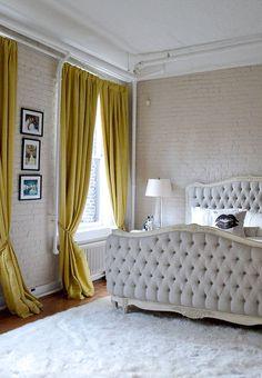 Soho NYC loft Tamra Sanford bedroom brick walls mustard drapes tufted bed