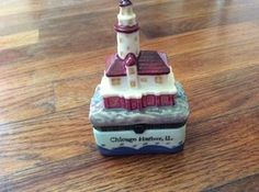 Collectible Hinged Trinket Box Porcelain Engrave Brass Lighthouse Chicago Harbor. What a Beautiful Piece. All these small Lighthouses are made of Porcelain Ceramic with  an Engraved Detailed Collar and Brass Hinge. So much Detail on such a small piece. This piece is about 4 inches high x 2 1/2 inches wide and 2 and 3/4 inches deep. This one is Chicago Harbor, each lighthouse has it City and State on the front of it. | Shop this product here: http://spreesy.com/comfortsofhome/213 | Shop all…