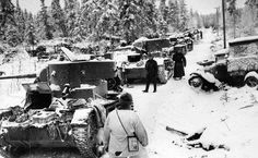 Finnish troops walk along a destroyed Soviet convoy of tanks and other armoured vehicles. Finland, 1940