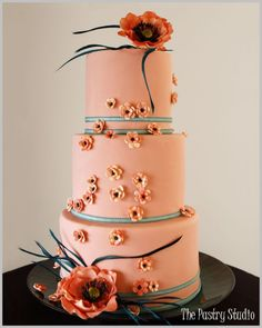 This stylish cake has a soft coral background with tone on tone sugar-paste florals. The flowers have chocolate brown centers. Accent colors were a soft aqua ribbon and turquoise feathers.