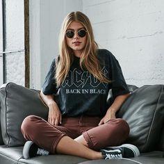 A t-shirt estampada pode ser a peça mais coringa do seu closet. T-shirt de banda preta, calça jeans marrom, tênis preto vans