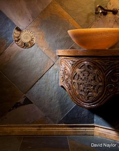 This bathroom wall has a bold and beautiful inset: an ancient ammonite from Madagascar, cut from a travertine ocean bed, sliced in half, and polished. It's surrounded by diagonal slate tiles, which unite earth and water tones, next to a stone bowl sink, hand-carved out of a solid block of agate. The curved, built-in base was created in our workshop.