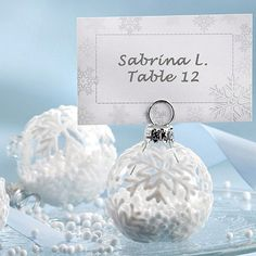 Monochromatic white ornaments, complete with snowflake escort cards, make an eye-catching display for a winter wedding. Decorate the baubles with snowflakes or simply fill them with powdered snow for a winter-wonderland effect. Be sure to purchase ornaments with flat bottoms, or affix a flat base, in order to make neat and readable rows.